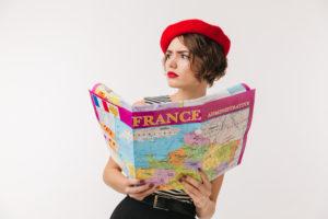 תרגום לצרפתית מאנגלית בתמונה: תיירת חובשת קובע אדום מחזיקה מפת צרפת