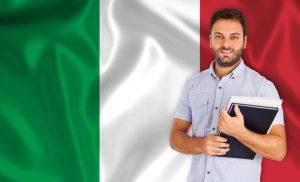 תרגום לאיטלקית בתמונה: סטודנט צעיר מחייך על רקע דגל איטליה אדום לבן ירוק