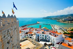 תרגום לספרדית בתמונה נוף לעבר חוף הים בספרד כחול על המצודה דגלים