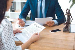 בתמונה: אישה וגבר ישובים על שולחן דנים בהסכם משפטי