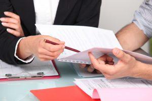 תרגום קורות חיים בתמונה: אישה וגבר אנשי עסקים מעיינים במסמכים