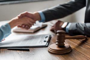 תרגום משפטי אישה וגבר לוחצים ידיים פטיש עץ על השולחן.