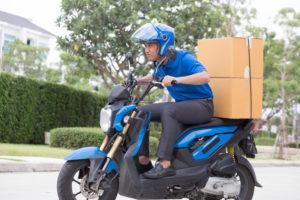 תרגום מסמכים מהיר בתמונה: משלוח מהיר קטנוע כחול רוכב עם קסדה וחולצה כחולה