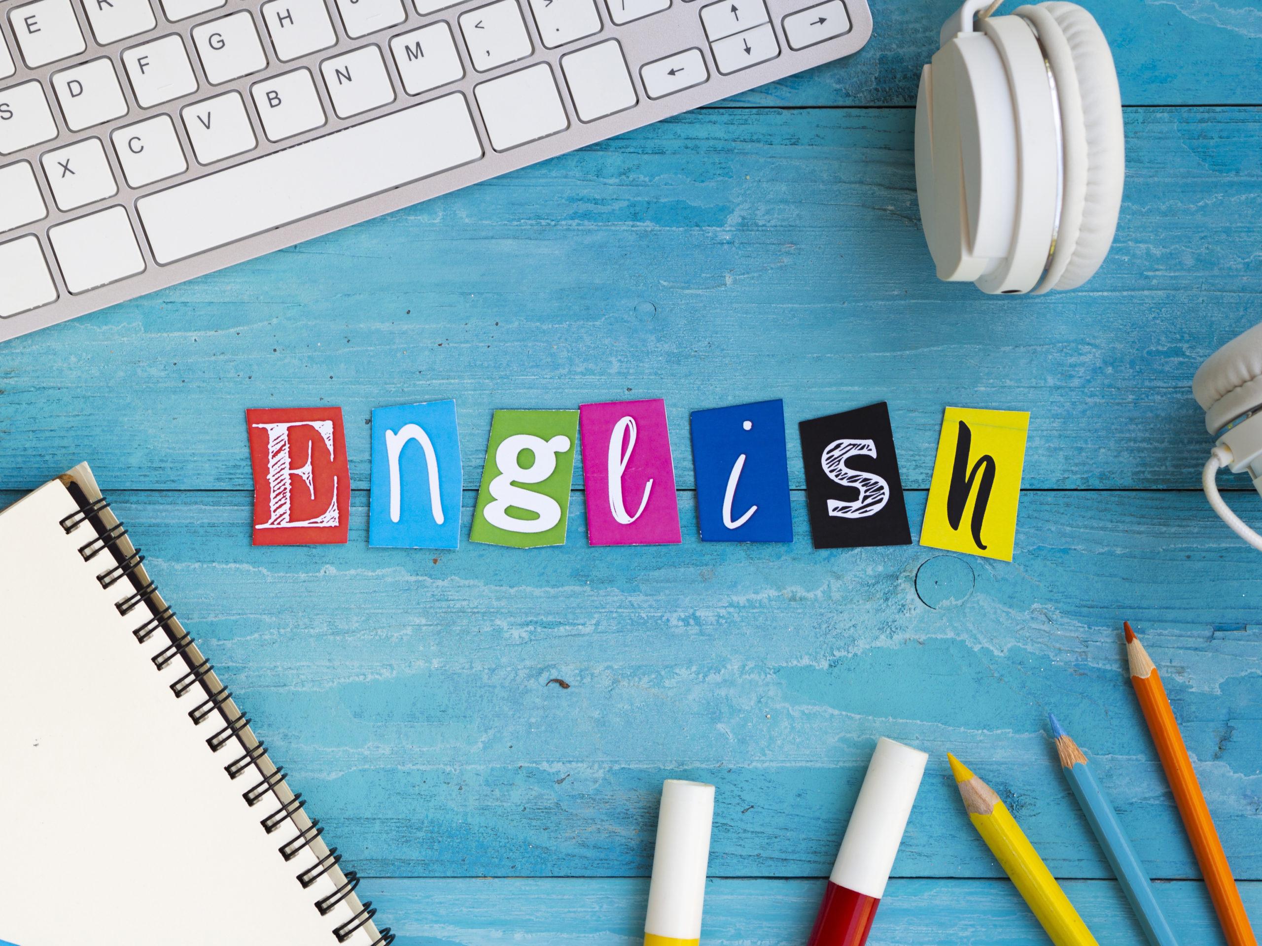 תרגום אתרי אינטרנט לאנגלית בתמונה על רקע המילה באנגלית באותיות בצבעים שולחן החלק מקלדת ועפרונות רואים בתחתית התמונה